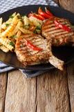 Ψημένη στη σχάρα μπριζόλα χοιρινού κρέατος με το κόκκαλο, το τσίλι και την κινηματογράφηση σε πρώτο πλάνο τηγανητών σε ένα plat Στοκ Φωτογραφίες