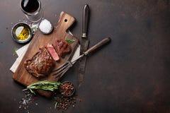 Ψημένη στη σχάρα ribeye μπριζόλα βόειου κρέατος με το κόκκινο κρασί, τα χορτάρια και τα καρυκεύματα Στοκ φωτογραφίες με δικαίωμα ελεύθερης χρήσης