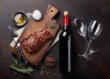 Ψημένη στη σχάρα ribeye μπριζόλα βόειου κρέατος με το κόκκινο κρασί, τα χορτάρια και τα καρυκεύματα Στοκ Φωτογραφίες