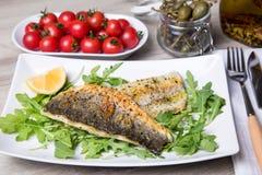 Ψημένη στη σχάρα seabass λωρίδα με το arugula, το λεμόνι, τις ντομάτες και τις κάπαρες στοκ φωτογραφία με δικαίωμα ελεύθερης χρήσης