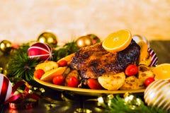 Ψημένη Χριστούγεννα πάπια που εξυπηρετείται με τις πατάτες, το πορτοκάλι και τις ντομάτες Στοκ Εικόνες