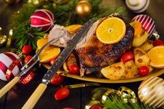 Ψημένη Χριστούγεννα πάπια που εξυπηρετείται με τις πατάτες, το πορτοκάλι και τις ντομάτες Στοκ Εικόνα