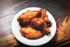Ψημένη bbq φτερών κοτόπουλου σχάρα στο πιάτο/καυτό και πικάντικο κοτόπουλο στο σκοτεινό υπόβαθρο στοκ εικόνα με δικαίωμα ελεύθερης χρήσης