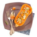 Ψημένη Butternut περικοπή κατά το ήμισυ παρουσιασμένος σε ένα πιάτο με τον παλαιό μαχαιροποιό στοκ εικόνες