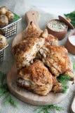 Ψημένοι μηροί κοτόπουλου που βρίσκονται σε έναν ξύλινο πίνακα με τα πράσινα και την πατάτα μωρών στοκ εικόνα