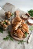 Ψημένοι μηροί κοτόπουλου που βρίσκονται σε έναν ξύλινο πίνακα με τα πράσινα και την πατάτα μωρών στοκ φωτογραφίες