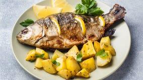 Ψημένος κυπρίνος ψαριών με τα πράσινα λεμονιών και πατάτες σε ένα πιάτο στοκ εικόνα