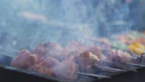 Ψημένος στη σχάρα shish kebab στο οβελίδιο μετάλλων Ο αρχιμάγειρας δίνει τη μαγειρεύοντας ψημένη σχάρα κρέατος με τα μέρη του καπ φιλμ μικρού μήκους