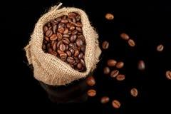 Ψημένος φασόλια καφές σε μια τσάντα, κινηματογράφηση σε πρώτο πλάνο στο μαύρο υπόβαθρο Στοκ Εικόνα