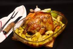 Ψημένο κοτόπουλο σε ένα φύλλο ψησίματος σε έναν σκοτεινό φούρνο στοκ εικόνα