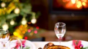 Ψημένο κοτόπουλο στον πίνακα Χριστουγέννων μπροστά από την εστία και δέντρο με τα φω'τα απόθεμα βίντεο