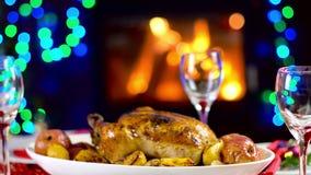 Ψημένο κοτόπουλο στον πίνακα Χριστουγέννων μπροστά από την εστία και δέντρο με τα φω'τα φιλμ μικρού μήκους