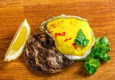 Ψημένο κοχύλι στρειδιών με το τυρί, τα εξυπηρετούμενα πράσινα και το λεμόνι Στοκ Εικόνες
