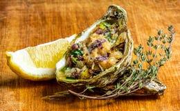 Ψημένο κοχύλι στρειδιών με το τυρί, τα εξυπηρετούμενα πράσινα και το λεμόνι Στοκ Φωτογραφία