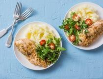 Ψημένο στήθος κοτόπουλου με τις πολτοποιηίδες πατάτες και arugula, σέλινο, σαλάτα ντοματών σε ένα μπλε υπόβαθρο Στοκ Εικόνες