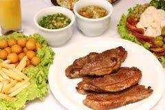 Ψημένο στη σχάρα βόειο κρέας με τις τηγανισμένες πατάτες και τη σαλάτα Στοκ Εικόνες