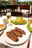 Ψημένο στη σχάρα βόειο κρέας με τις τηγανισμένες πατάτες και τη σαλάτα Στοκ Εικόνα