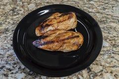 Ψημένο στη σχάρα κοτόπουλο σε ένα μαύρο πιάτο στο μετρητή Granit στοκ φωτογραφία