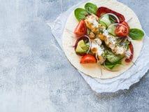 Ψημένο στη σχάρα κοτόπουλο στα οβελίδια μετάλλων με την ελληνική σάλτσα και φρέσκα λαχανικά στο pita casserole ελληνικά κομματιασ στοκ εικόνα