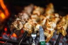 Ψημένο στη σχάρα κρέας βόειου κρέατος στη σχάρα με το δίκρανο και το μαχαίρι κοντά επάνω, σχάρα, shashlik, kebab, οβελίδιο στη σχ Στοκ εικόνες με δικαίωμα ελεύθερης χρήσης