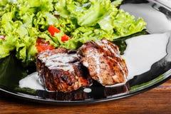 Ψημένο στη σχάρα κρέας μπριζόλας με τη σαλάτα, τις ντομάτες και τη σάλτσα φρέσκων λαχανικών στο μαύρο πιάτο, ξύλινο υπόβαθρο Στοκ Φωτογραφίες
