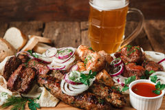 Ψημένο στη σχάρα κρέας που εξυπηρετείται με την κούπα κρύου στενού επάνω μπύρας Στοκ Εικόνες