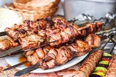 Ψημένο στη σχάρα κρέας kebabs στο άσπρο πιάτο Σουβλισμένος στο ξύλινο κρέας χοιρινού κρέατος ραβδιών νόστιμο Shashlik ή Shish keb Στοκ φωτογραφία με δικαίωμα ελεύθερης χρήσης