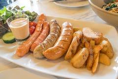 Ψημένο στη σχάρα λουκάνικο μιγμάτων με την τηγανισμένα πατάτα και τα λαχανικά Στοκ εικόνα με δικαίωμα ελεύθερης χρήσης