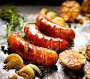 Ψημένο στη σχάρα λουκάνικο με την προσθήκη του σκόρδου και των κρεμμυδιών Στοκ Εικόνα