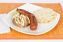 Ψημένο στη σχάρα λουκάνικο με το arepa και τη μαγειρευμένη πατάτα Στοκ φωτογραφία με δικαίωμα ελεύθερης χρήσης