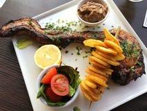 Ψημένο στη σχάρα πλευρό χοιρινού κρέατος, λαχανικά και τηγανισμένες πατάτες στο άσπρο πιάτο Στοκ φωτογραφία με δικαίωμα ελεύθερης χρήσης