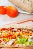 Ψημένο στη σχάρα σάντουιτς κοτόπουλου με το μαρούλι και το κρεμμύδι ντοματών Στοκ Φωτογραφία