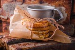 Ψημένο στη σχάρα σάντουιτς τυριών σε χαρτί με το φλυτζάνι καφέ στον ξύλινο πίνακα Εκλεκτική εστίαση Στοκ Φωτογραφία