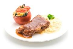 ψημένο στη σχάρα χοιρινό κρέας πλευρών με τις πατάτες πολτοποίησης και σπανάκι που ψήνεται στην ντομάτα Στοκ Εικόνα