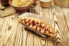 Ψημένο στη σχάρα σχάρα χοτ-ντογκ με τη σάλτσα, χοτ-ντογκ με την κίτρινη μουστάρδα, Στοκ Εικόνα