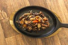 Ψημένο στη σχάρα χταπόδι με τα μαύρα λαχανικά skillet στοκ φωτογραφία