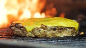 Ψημένο στη σχάρα cutlet με το τυρί, burger, cutlet χάμπουργκερ, στο υπόβαθρο μια φλόγα, πυροβολισμός κινηματογραφήσεων σε πρώτο π απόθεμα βίντεο