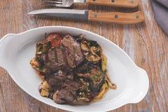 Ψημένο στη σχάρα tenderloin κρέατος με το μαγειρευμένο ψημένο πιάτο λαχανικών και χορταριών Στοκ Εικόνες
