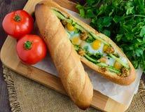 Ψημένο τριζάτο baguette με τα τηγανισμένα αυγά, τα αγγούρια και τα πράσινα Στοκ φωτογραφίες με δικαίωμα ελεύθερης χρήσης