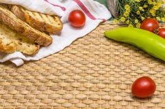 Ψημένο ψωμί στο άσπρο ύφασμα στο χαλί θέσεων αχύρου με τις ντομάτες κερασιών, το πράσινο πιπέρι, και τα λουλούδια Στοκ Εικόνες