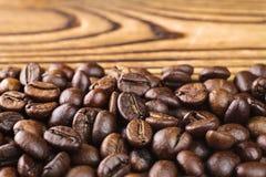 Ψημένο arabica φασολιών καφέ στον ξύλινο πίνακα, κινηματογράφηση σε πρώτο πλάνο, εκλεκτική εστίαση Στοκ Εικόνες