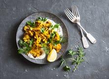 Ψημένο turmeric κουνουπίδι με την ελληνική σάλτσα γιαουρτιού Εύγευστο υγιές πρόχειρο φαγητό σε ένα σκοτεινό υπόβαθρο Στοκ εικόνες με δικαίωμα ελεύθερης χρήσης