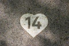 Ψηφίο 14 που χρωματίζεται στην άσπρη καρδιά σε ένα πεζοδρόμιο Στοκ Εικόνες