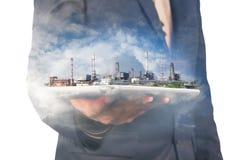 Ψηφιακή ασύρματη ταμπλέτα λαβής επιχειρηματιών με τις εγκαταστάσεις διυλιστηρίων πετρελαίου Στοκ εικόνα με δικαίωμα ελεύθερης χρήσης