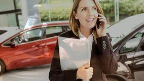 Ψηφιακή ζωτικότητα της θηλυκής εκτελεστικής ομιλίας πωλήσεων στο τηλέφωνο στην αίθουσα εκθέσεως αυτοκινήτων απόθεμα βίντεο