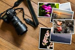 Ψηφιακή κάμερα DSLR και σωρός των φωτογραφιών στο εκλεκτής ποιότητας ξύλινο υπόβαθρο grunge στοκ φωτογραφία με δικαίωμα ελεύθερης χρήσης