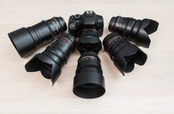 Ψηφιακή κάμερα SLR και μερικοί ανταλλάξιμοι χειρωνακτικοί φακοί Ο εξοπλισμός για τη κινηματογραφία Ο ξύλινος πίνακας στοκ φωτογραφίες