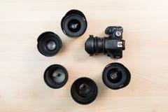 Ψηφιακή κάμερα SLR και μερικοί ανταλλάξιμοι χειρωνακτικοί φακοί Ο εξοπλισμός για τη κινηματογραφία Ο ξύλινος πίνακας στοκ εικόνες