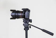 Ψηφιακή κάμερα SLR σε ένα τρίποδο με έναν μετακινούμενο χειρωνακτικό φακό σε ένα γκρίζο υπόβαθρο Πυροβολισμός στο εσωτερικό στοκ φωτογραφία