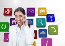 Ψηφιακή σύνθετη εικόνα της επιχειρηματία που μιλά στο τηλέφωνο με τα εικονίδια εφαρμογής στο υπόβαθρο Στοκ Φωτογραφία